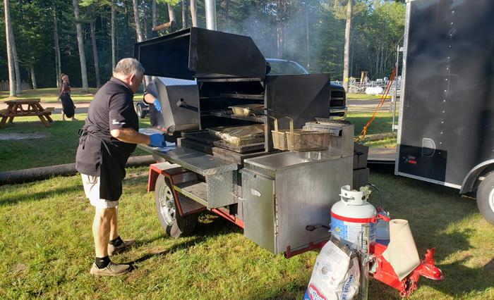 Man at bbq pit cooking wild game